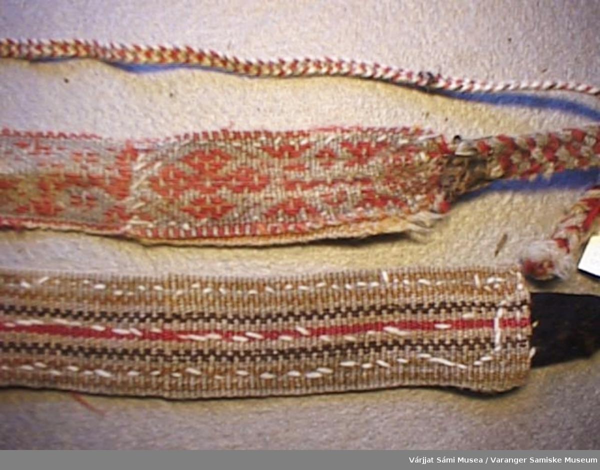 Komagbånd vevd på grindvev av ull og bomullsgarn i fargene rød, hvit og blå. Kort fletting i den ene enden (til å feste i komagen) og lang fletting i den andre (til å surre rundt leggen).