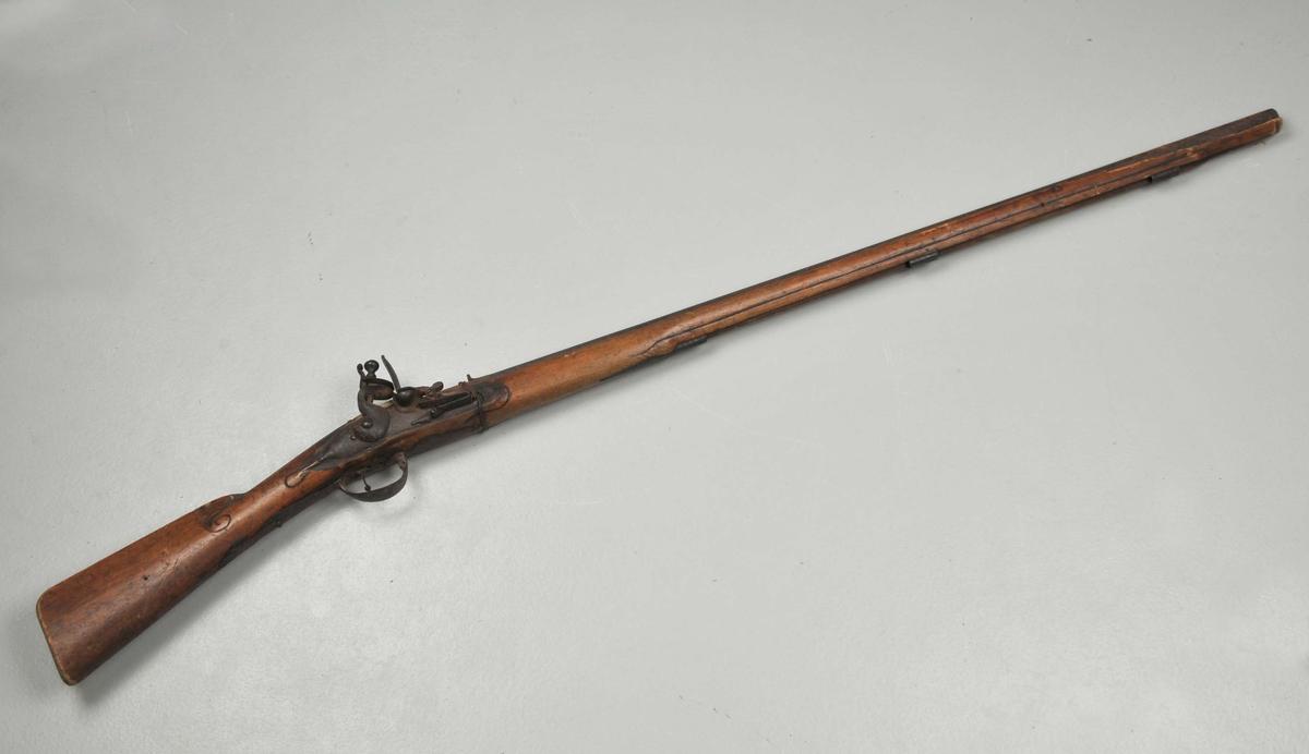 Avtrekkar og  og avtrekkarbøyle er av jern. Bøylen har jernbeslag og er ca. 30 cm lang. Festelåsen til laupet er borte. Børsa har flintlås.  Tre festebøylar til ladstokk, men stokken manglar.
