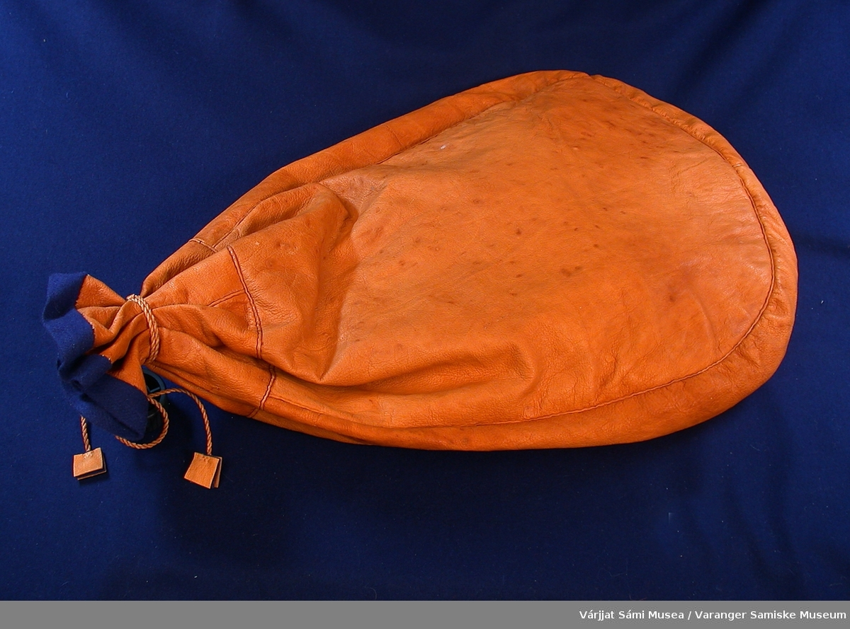 642-1: Sekk av reinskinn. Ser ut som en stor kaffepose: åpning i toppen med snøring av tvunnede skinnsnorer. Ca. 45 cm lang.  642-2: B: Veske av reinskinn med tinntrådbroderi i fronten, på lokket/klaffen. Veska har halvmånefasong. Den lukkes med en tvunnet skinnsnor som tres over en avlang treperle med horndetaljer. Skulderreima er av fletta skinn. Bredde: 23 cm, høyde: 15 cm.  .