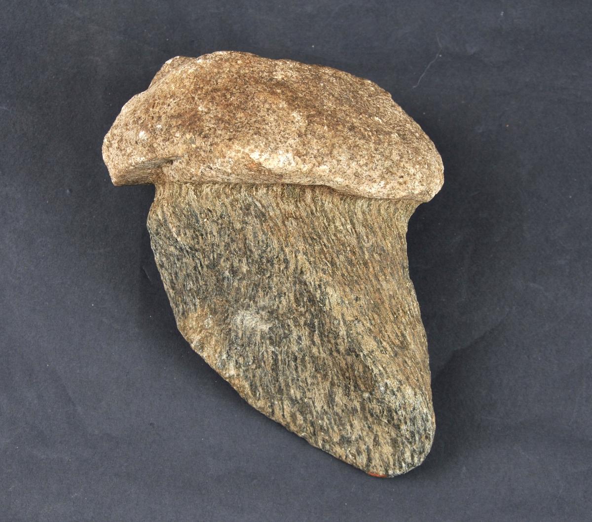 Tilhoggen fallosforma stein. Spiss i nedre enden.