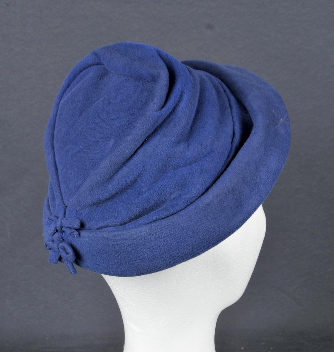 Filthatt med oppbretta brem. Pull med innfelt toppstykke, skrånande bakover. Nakkesaumane er pynta med to små sløyfer i same stoffet som hatten.Festestrikken er øydelagt.