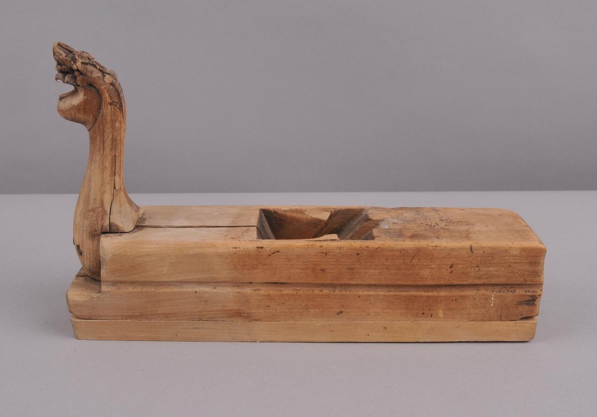 Handhøvel i tre. Handtaket er skore ut og har form som eit løvehovud.