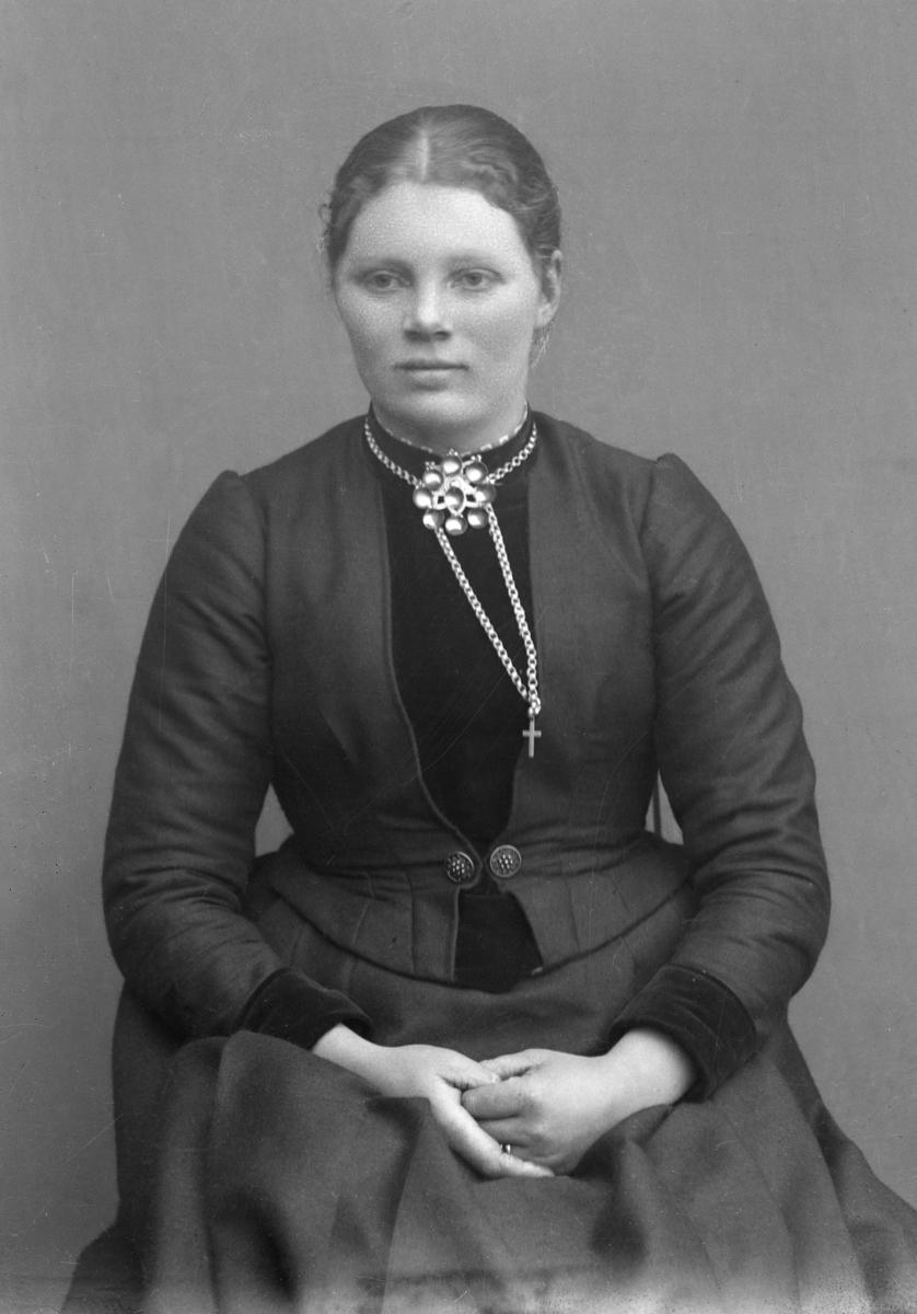Kvinne kledd i mørk kjole, med sølje, sittende foran lerret