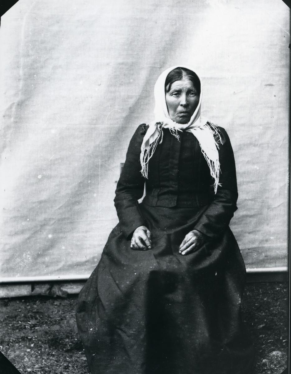 Eldre kvinne i mørk kjole og lyst skaut, sittende foran lerret