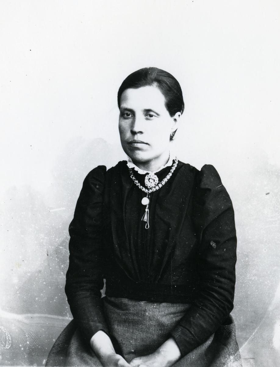 Kvinne sittende foran lerret, halvfigur