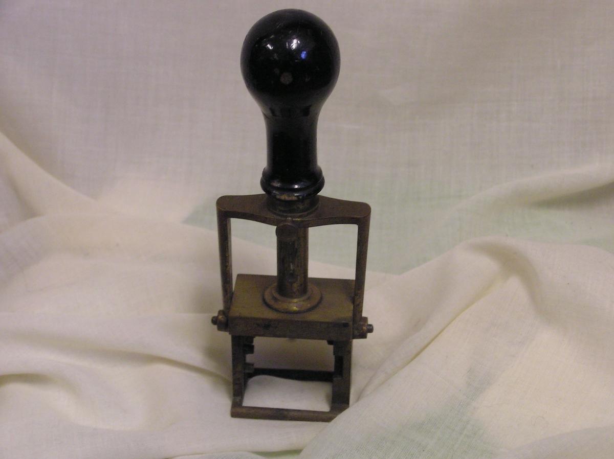 Form: rekt. stativ  m.oval stempelplate som må trykkes ned; tre håndtak