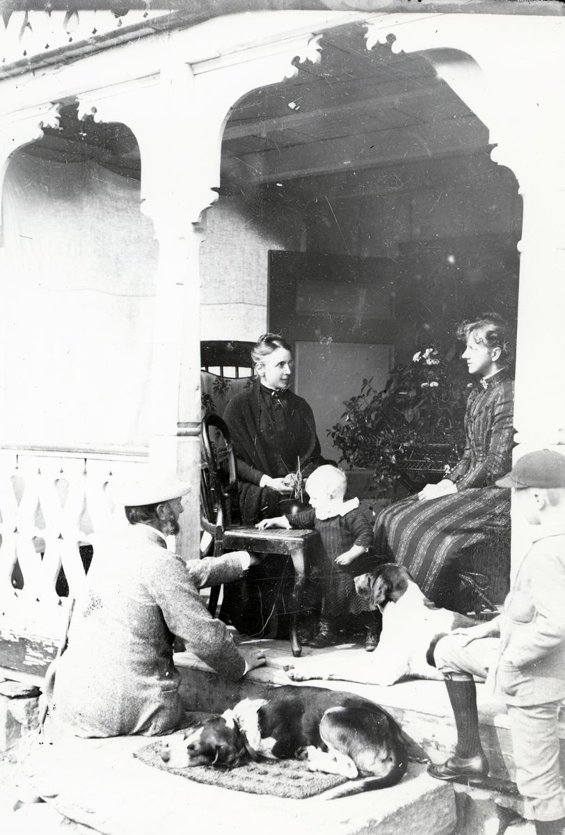 To kvinner, den ene med strikketøy, to barn, to hunder og en mann, fotografert i inngangsparti med sveitserstilsdekor