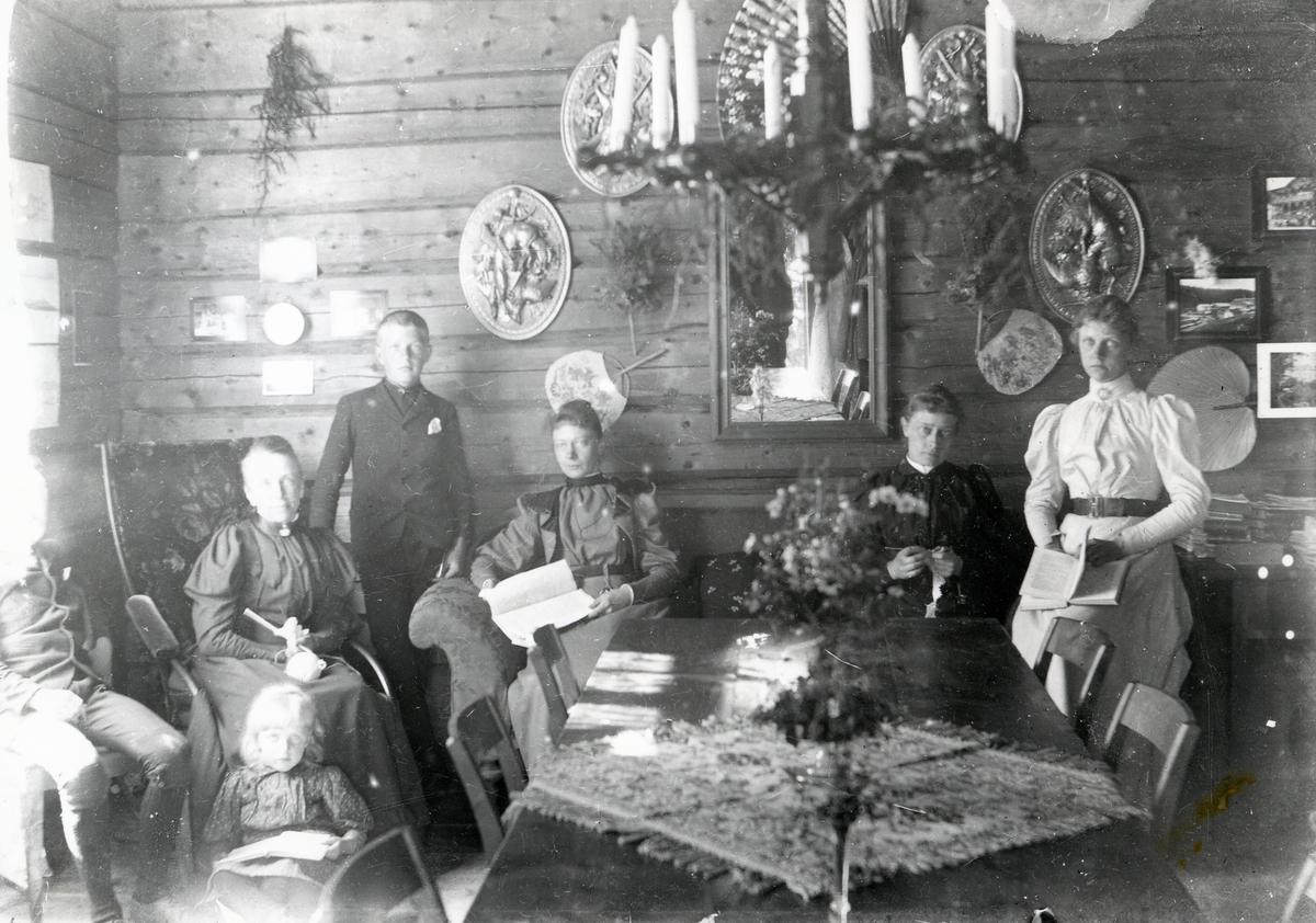 Mennesker i interiør, med blant annet gyngestol, sofa, spisebord og lysekrone
