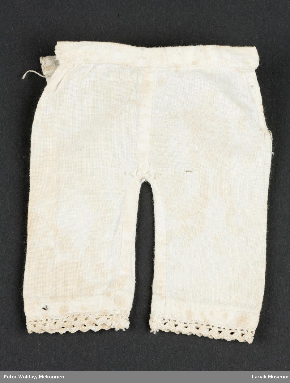 Liten dukke underbukse med blondekant nederst. Åpning i begge sider