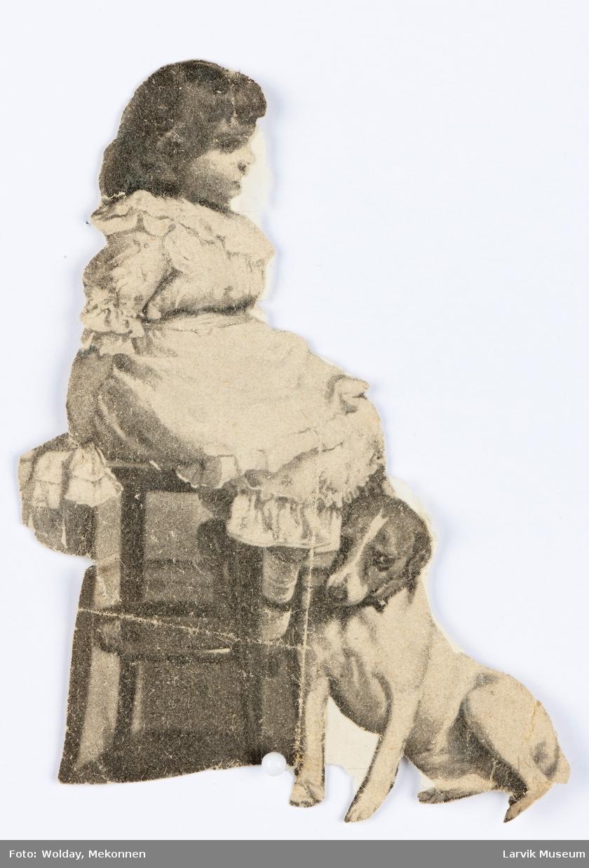 Liten jente i blondekjole sitter på en høy stol. En liten hund lener seg mot bena hennes.