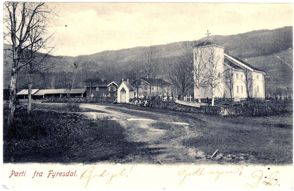 """Moland kirke og Moland Prestegård i Fyresdal. Den låge uthusrekka til venstre vart rive i 1917 då det vart bygd nytt uthus. """"Drengestoga"""" til venstre for kyrkjegardsporten brann i 1920."""