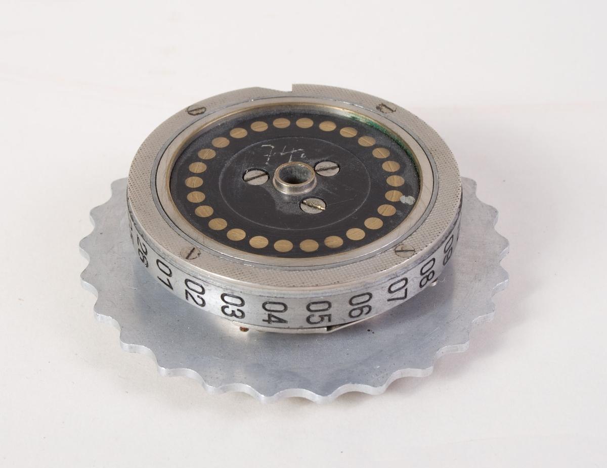 Rektangulær trekasse med lokk som er hengslet fast i selve kassen.  Kassen er utstyrt med en lukkemekanisme.  For å åpne må en hendel presses til høyre. Inne i boksen ligger to sirkelformede hjul med tagger.  Hjulene er på den ene siden merket med tall. I lokket er det limt to knapper av filt - antagelig for å holde hjulene på plass i boksen.