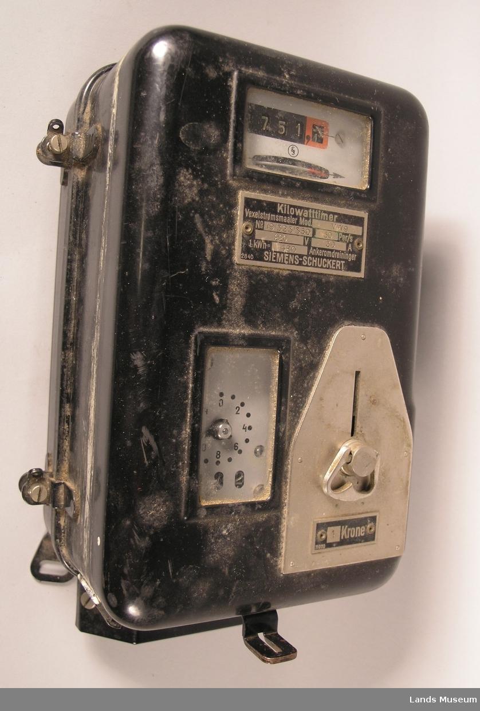 Apparatet har innkast for 1-kronemynter. Det har også en måler som viser kilowatt-timer. Apparatet har hengt på vegg.