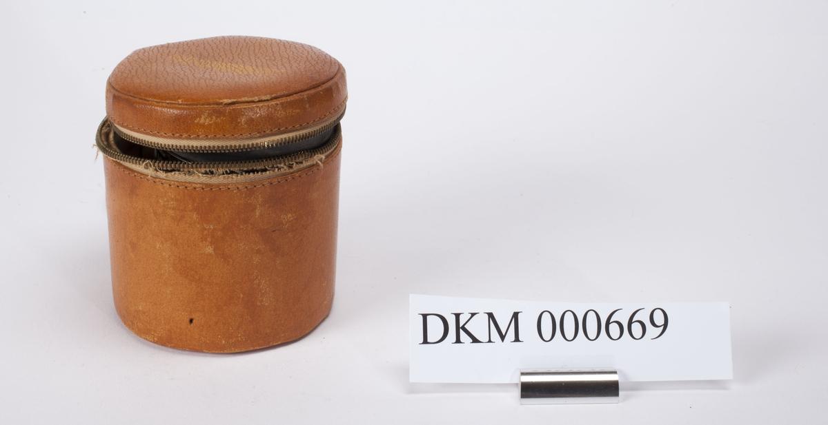 Metallsylinder med gummi i den ene enden. Apparatet er batteridrevet og har en bryter for måling av desibel og en bryter for måling av frekvens. Sylinderformet etui med glidlås.