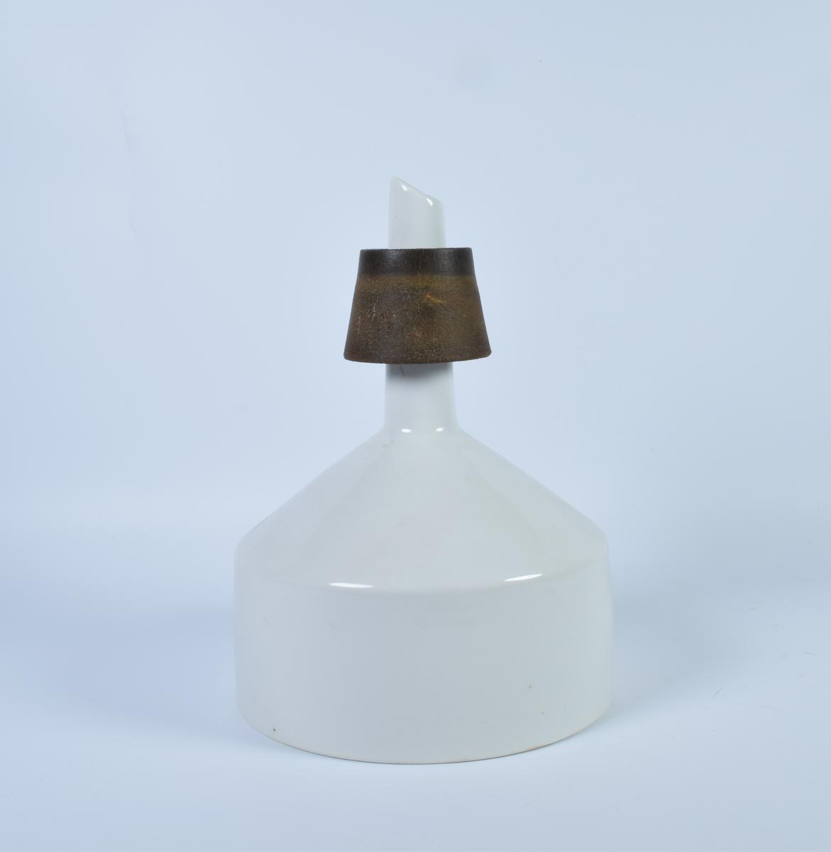 """Filtreringstrakt i hvit keramikk. I """"bunnen"""" av trakten er det mange små hull som fører til et rør. Rundt røret er det en tykk ring av gummi. Trakten kan settes rett oppi en flaske. Ved filtrering la man oppi et filterpapir (metitta-filter)."""