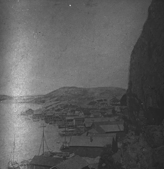 """""""Fjällbacka. Fjällbacka fiskeläge nere vid foten av berget, med sjöbodar och fiskebåtar."""""""