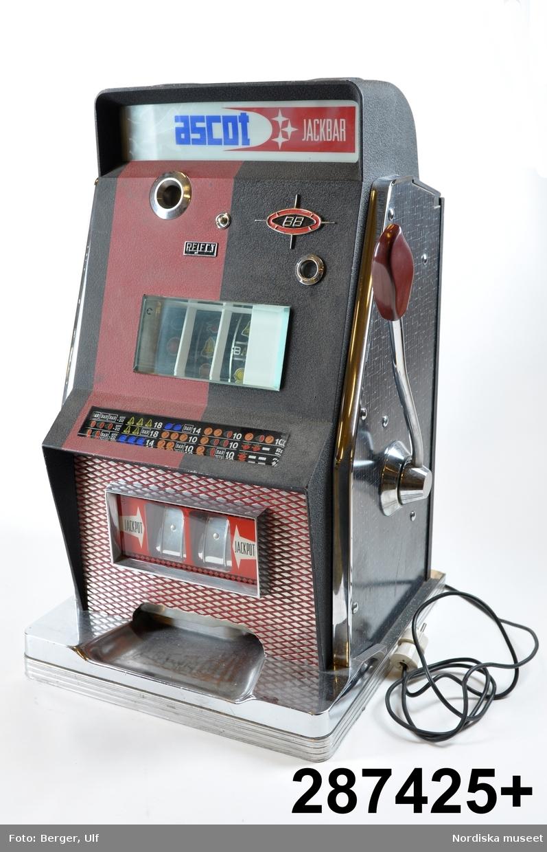 """Inventering Sesam 1996-1999: L 46 cm B 44,5 cm H 74 cm Spelautomat, enarmad bandit. Hölje av svart och röd metall och svartvit perstorpsplatta. Stående på träplatta med vitmetall. Framtill olika skyltar bakom tjockt glas. Mitt på (eg. innuti) tre rullar med olika symboler, t ex apelsiner, halva meloner, siffror mm, bakom glas. På vänster sida hål för mynt. På höger sida en arm med rött handtag av backelit. På vänster sida elektrisk sladd med vit kontakt.  Text på skyltarna text """"ASCOTT JACKPOTT"""", """"Reject"""", Jackpott"""" och karta med de olika symbolkombinationer som man vinner på. Innuti mekanism av metall. Öppningsbart bakstycke (med nyckel vilken saknas vid inv. 1998)  Liten svart skylt nertill på vänster sida; """"Ascott s.p.a. / Calenzo - Florence Italy / Tipo 88 / M.la 067"""" Funktion; man stoppar in ett mynt (troligen 1 krona) och drar i armen. Rullarna med de olika symbolerna surrar och stannar sedan en och en (går ev att själv stoppa med en liten knapp mitt på framsidan). Om man lyckas få någon av de kombinationer som finns på skylten så vinner man pengar, som kommer ut längst ned. Mest vinner man om man får tre lika symboler. Enarmade banditer har varit vanliga på motell, konditorier, bensinstationer och dyl. 1973 fanns ca 140 000 spelautomater, samma år infördes skatt på automaterna. Senare blev de förbjudna.  Jmfr liknande enarmad bandit av samma tillverkare (?) inv.nr 287.426 Bilaga Leif Wallin feb 1998"""