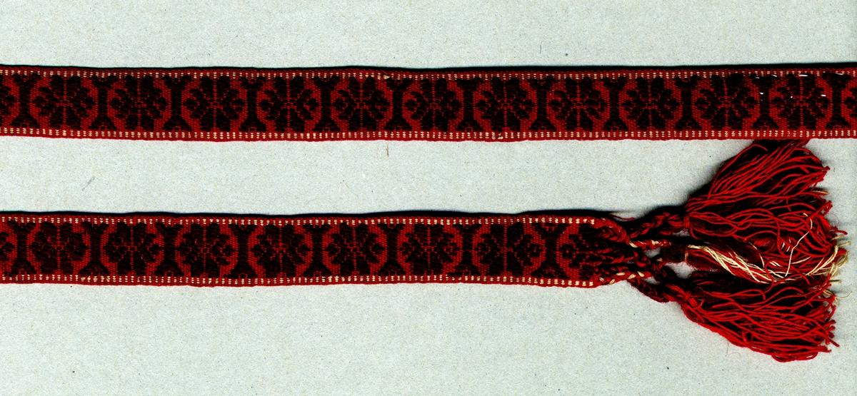 """Band vävt i opphämta. Röd botten med brunrött opphämtamönster och vita tvistränder på var sida. Avslutat i var ände med tofsar (55 mm långa); varptrådarna är flätade och avslutade med iknuten frans av brunrött ullgarn samt rött och oblekt bomullsgarn. Varp, botten i rött och oblekt 2-trådigt s-tvinnat bomullsgarn. Varp, mönster i brunrött (vinrött) 2-trådigt s-tvinnat ullgarn. Tre bottenvarptrådar mellan varje mönstervarptråd. Inslag i rött 2-trådigt s-tvinnat bomullsgarn, 17 inslag/cm. Märkt med påsytt tygband med texten: """"Hanna Mim Veberöd"""". Längd inklusive fransar."""