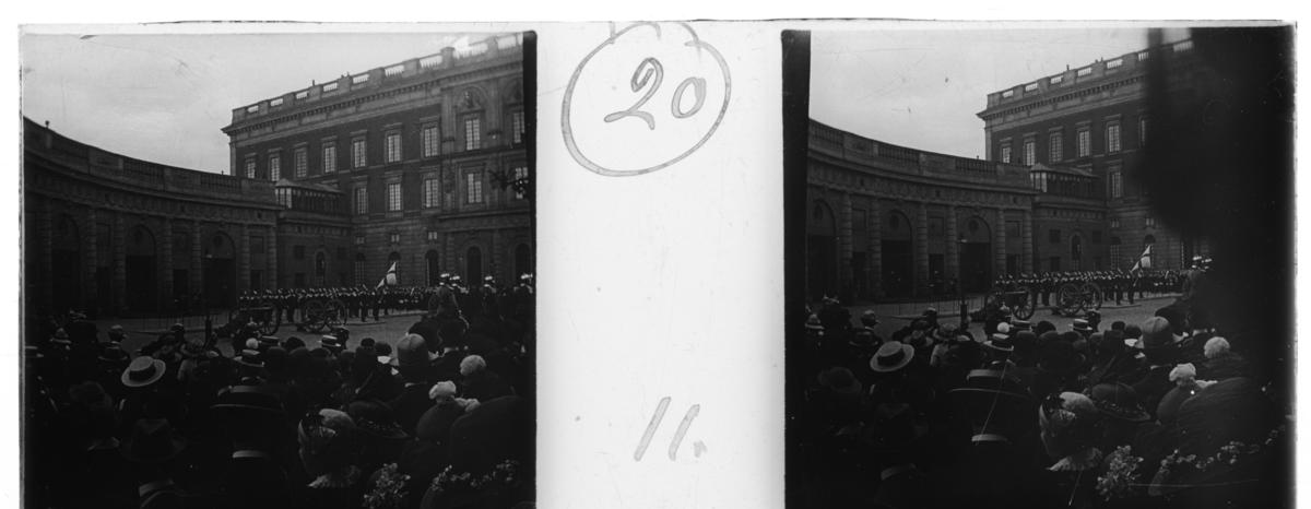 'Vy med vaktavlösning framför slottet med fana, kanoner och beridna vakter. Åskådare med ryggar mot kameran. :: Enligt text till fotot: ''Changing guard at the palace. Hästgardet marches off.'' (Vaktavlösning vid slottet. Hästgardet marscherar iväg.) ::  :: Ingår i serie med fotonr. 5247:1-20, se även hela serien med fotonr. 5237-5267.'