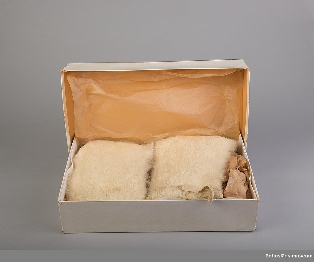 """Vit kaninpäls. Fodrade med olika rutiga foder; skotskrutigt foder på den ena och rött/vitt/svart-rutigt på den andra. Två band i varje mössa av beige silkesrips för att knyta under hakan; längd 20 cm, bredd 2 cm.  Mössorna ligger i pappkartong 41,5 x 27 x 10 cm. Vit botten med brun kant på locket samt etikett i var ände text på den ena: """"Barnstrumpor 2166/5 blått"""" och på den andra: """"HSLR 1156/11FG""""?. Locket trasigt. Lagat med sytråd på ett ställe klisterlapp med text: """"157 u 85/5"""". Personuppgifter UM023791"""
