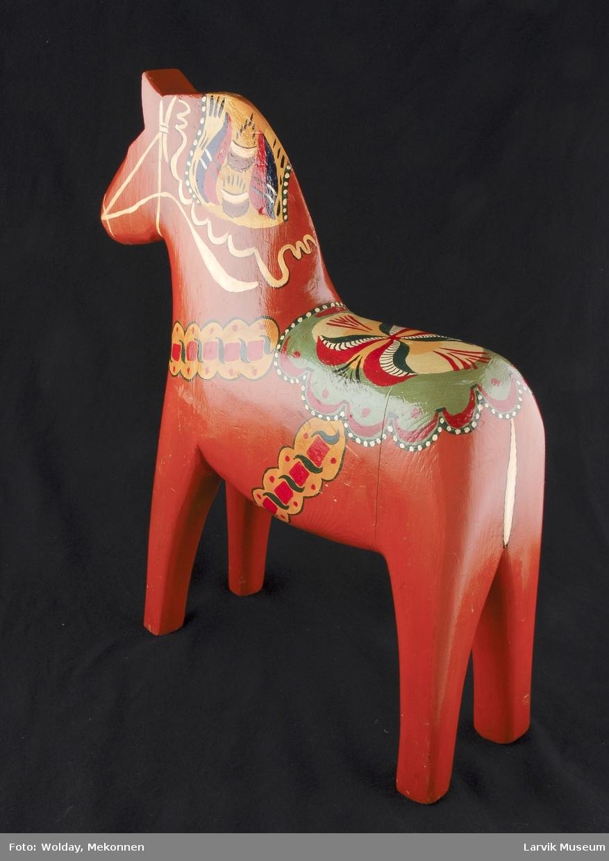 Form: Stor utskåret hest i tre, sølvskilt i front.