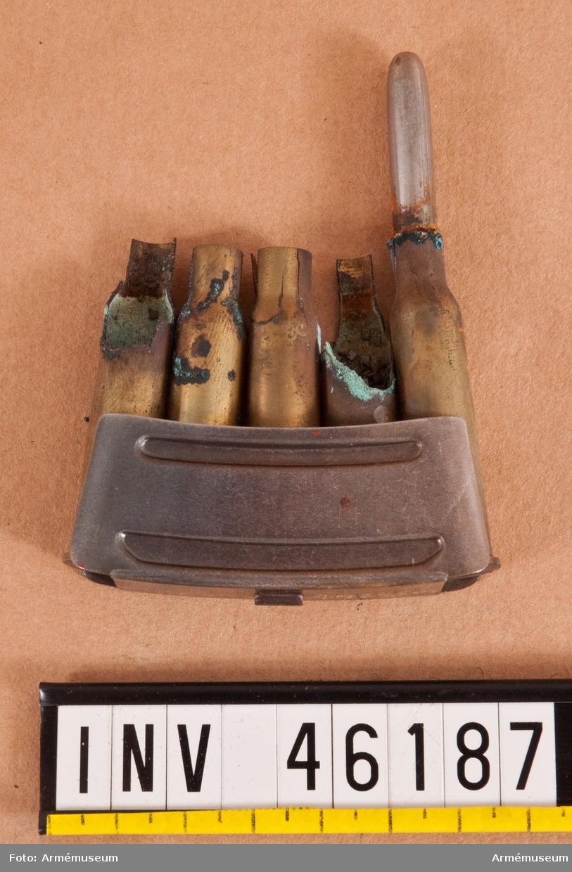 Grupp E V. Patron(hylsa) till 6,5 mm gevär fm/1891 av Mannlichers system. Ursprungligen skarp patron, nu korroderad och sönderfallen.