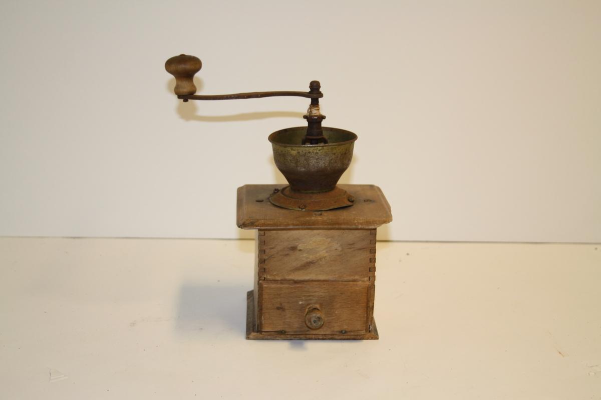Kaffekvern i tre og metall. Firkanta/kubisk kasse med laus skuff i botn til ferdigkverna kaffe. Traktforma topp med S-forma jernsveiv øverst påsatt dreid treknott.