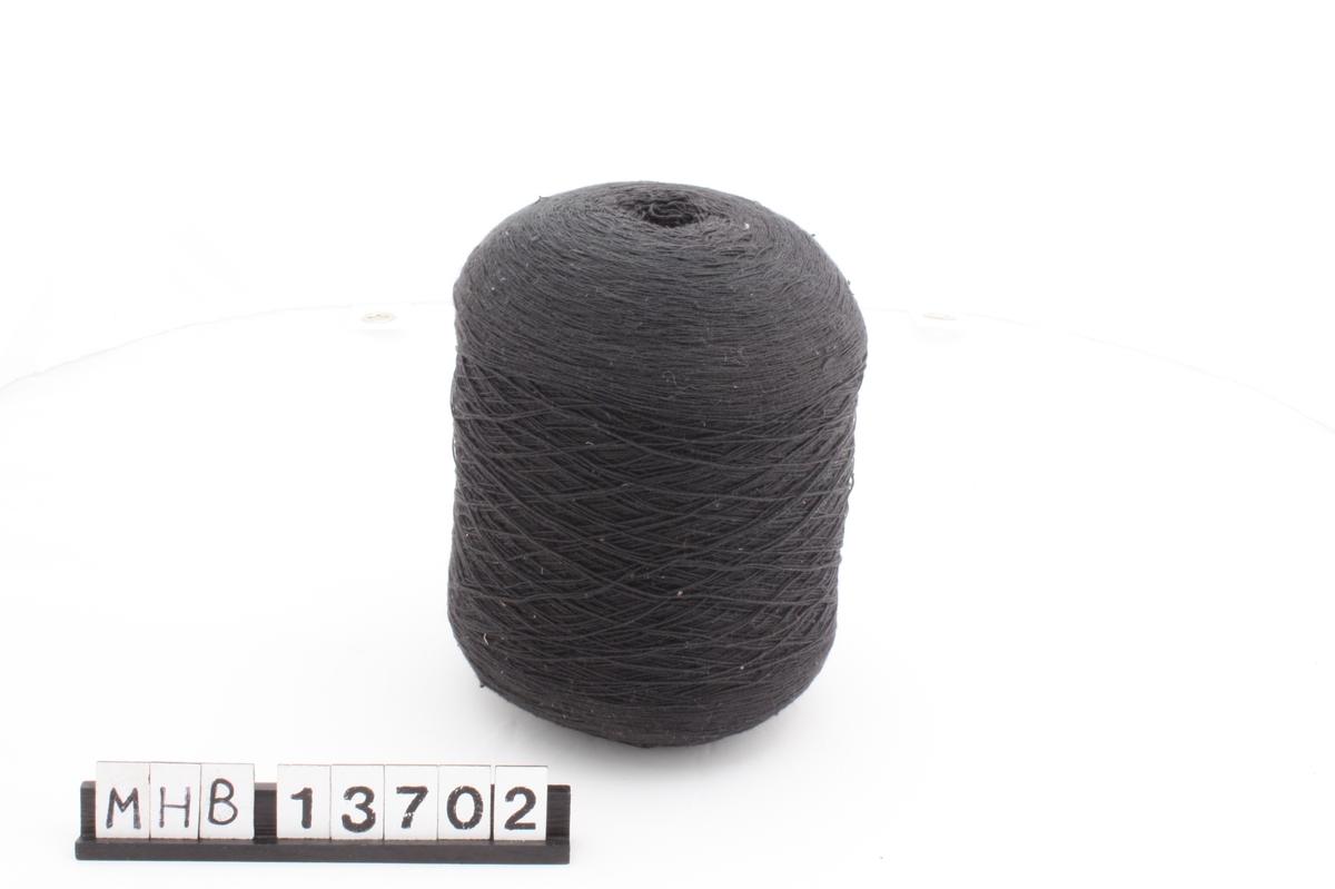 Svart, tynn og tettspunnet bomullstråd som er spunnet rundt et sylindrisk papphylster slik at den danner et nøste.