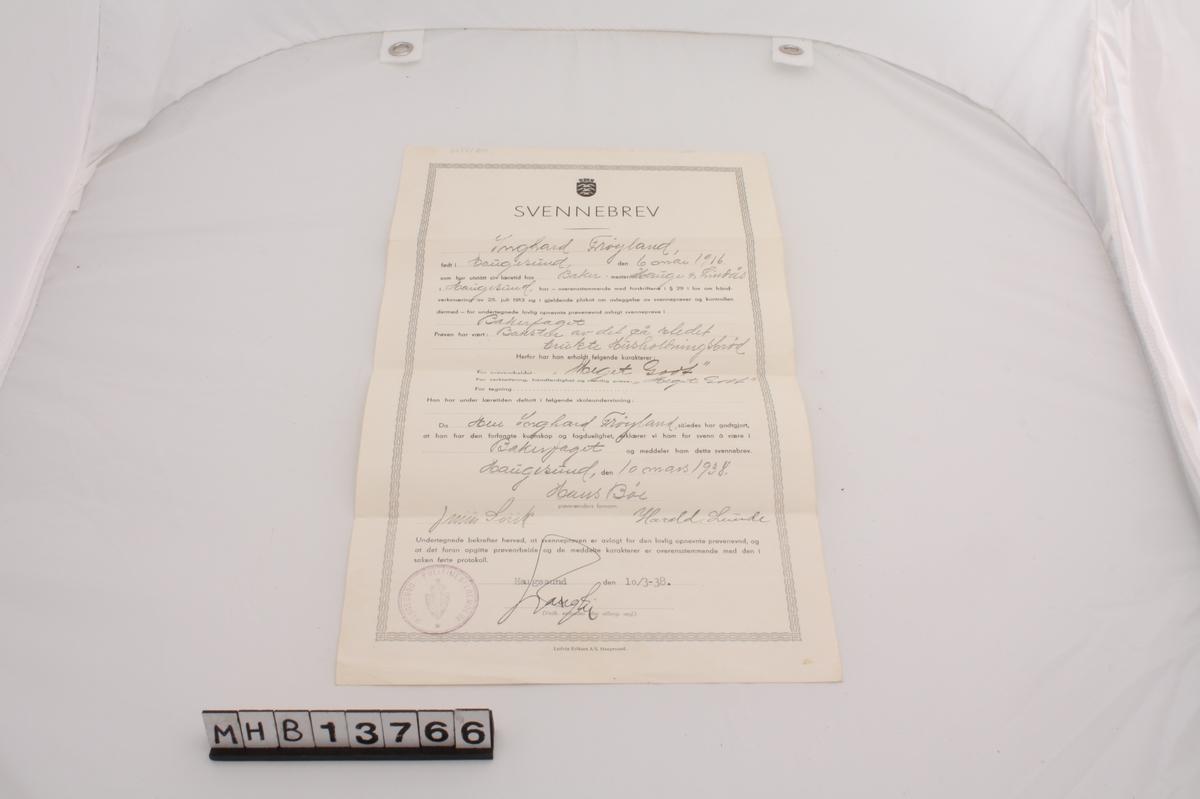 Svennebrev på enkelt, rektangulært ark for bakerfaget. Teksten på brevet er rammet inn av en bølget bord av stiplede streker, og øverst er Haugesunds kommunevåpen. Brevet er stemplet nederst i venstre hjørne av Haugesund Politimesterembede.