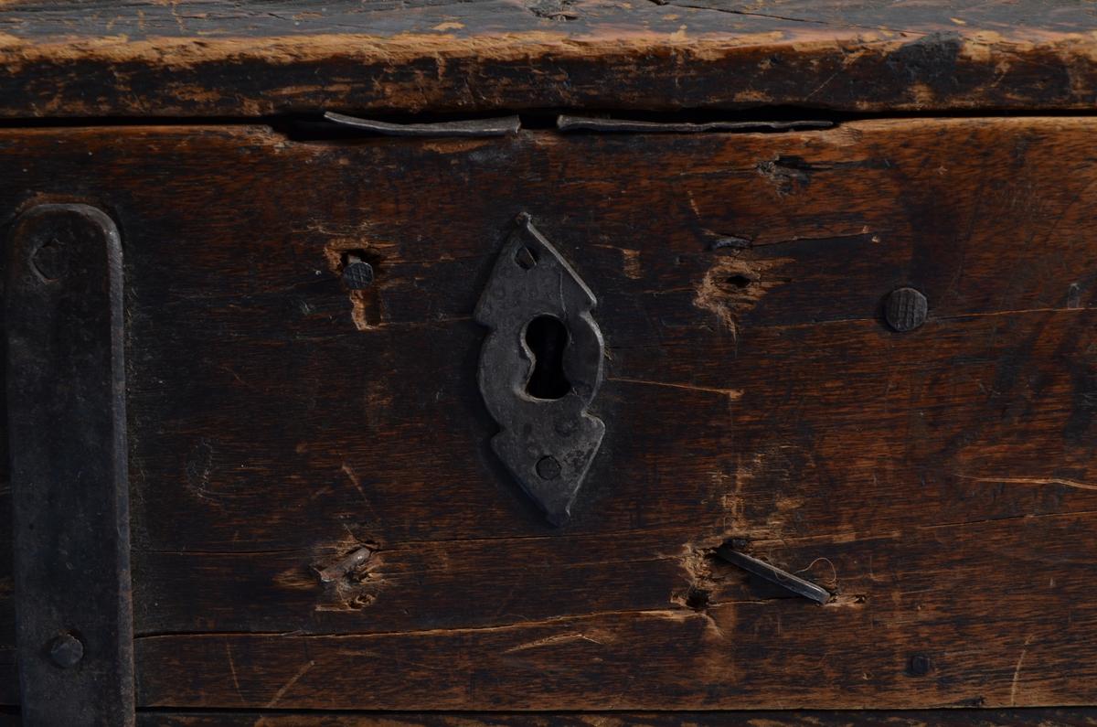 Feleskrin av Bjørk. Bunnen er festet til sidene med to lange beslag helt fra øverste kant fram til gangjern. Videre er jernet festet på innsiden av lokket. Det korte endestykket er festet med to jernbeslag. Jernhempe med ring i begge kortender. Liten lås på fremsiden.  Rester etter brun-svart maling på skrinet. Små hakk i kantene. Lokket er er oppbuet og har en profilert rand langs kanten.
