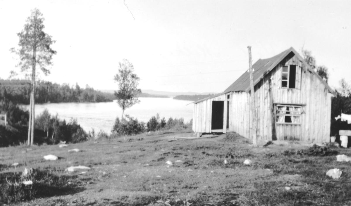 """""""Ved Melkefoss i Pasvig."""" Et hus. Elva i bakgrunnen."""