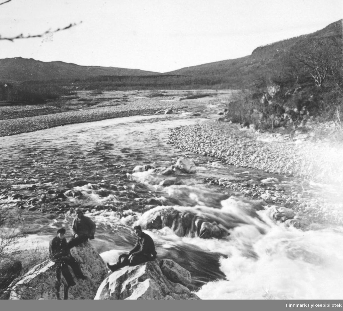 Landskapsbilde fotografert fra Laksefjord. Føran bildet sitter tre menn. Bildet er et stereobilde.