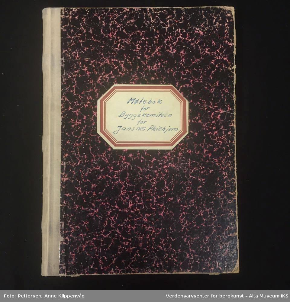 Rektangulær notatbok, innbundet med harde permer. Rosa og sortmønstret på forsiden og baksiden. Inneholder vedtak fra møtene for byggekomiteen for Jansnes pleiehjem.