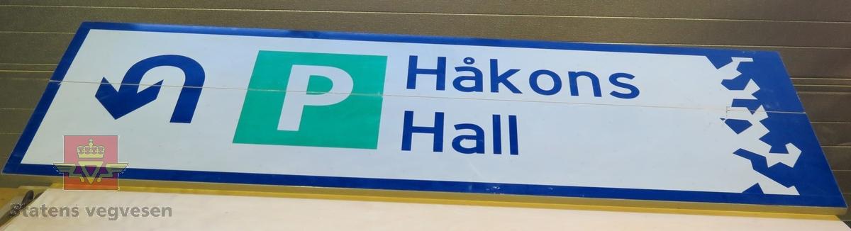 """Rektangulært skilt av aluminium. Har symbol for parkering og kjøreretning samt teksten """"Håkons hall"""". Flerfarget, med grå bakside."""