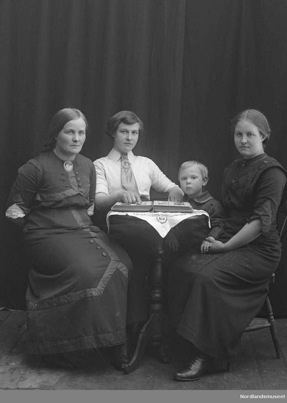 Portrett. 4 personer sitter sitter rundt et bord. Tre kvinner i 20-åra. En gutt ca. 7 år.