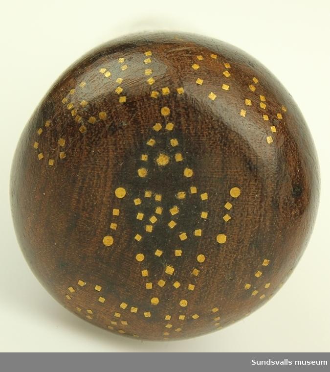 Lång konformad träpik. På ovansidan har små kvadratiska guldkolorerade ornament lagts in.