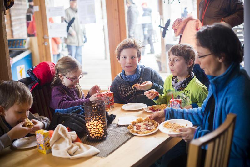 Barn og voksne spiser vafler.