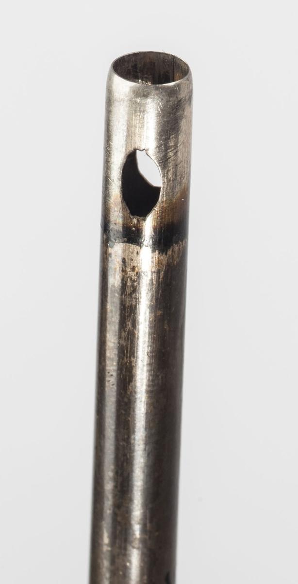 """Syllignende gjenstand. Spiss med svart treskaft. I tillegg en metallsylinder med hull og en kortere """"metalltopp""""."""