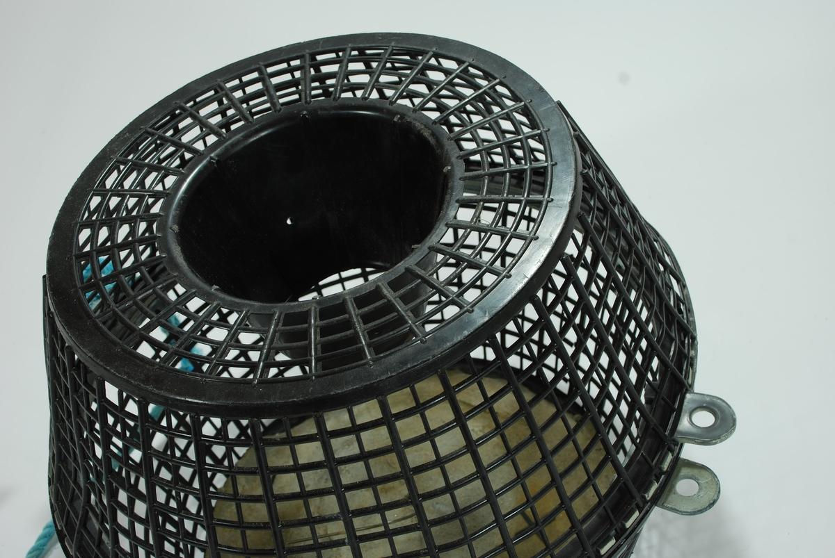 En forenklet versjon av de tradisjonelle fall-fellene hvor garnet er erstattet av hård-plast. Todelt bøtte-tene med topp og bunn. Form og materiale kan minne om en skittentøyskurv.  Rutemønstret, sort hardplast.  Betongblokk i bunnen til synkemateriale. Dekker hele bunnen. Små biter faller av i kantene.  Agnspyd av metall er støpt inni betongen. Fallbøtte i toppen. Både topp og bunn har randkant i hard gummi med tapper som vris i hverandre for å lukke tena. Turskis nylontau er festet i disse.