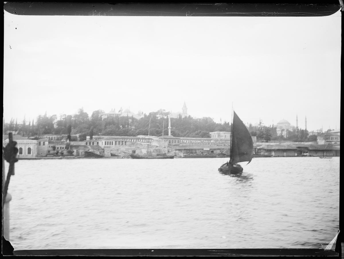 """""""Jerusalem 10, Cairo 6"""" (inskr eske). By ved havet. En seilbåt på havet."""