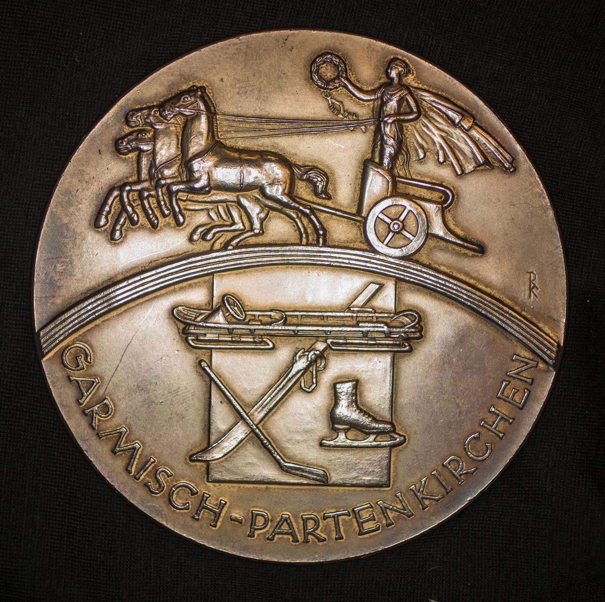 På adversen er motivet de olympiske ringer. Rundt disse langs kanten teksten: IV. OLYMPISCHE WINTERSPIELSEN, og to stjerner. På reversen er motivet en mann med kappe og larbærkrans stående i ei vogn trukket av tre hester. Vogn og hester kjører over regnbuen. Under denne en bobslede, ei ski, ei ishockeykølle og ei skøyte. Under regnbuen langs kanten står det: GARMISCH-PARTENKIRCHEN.
