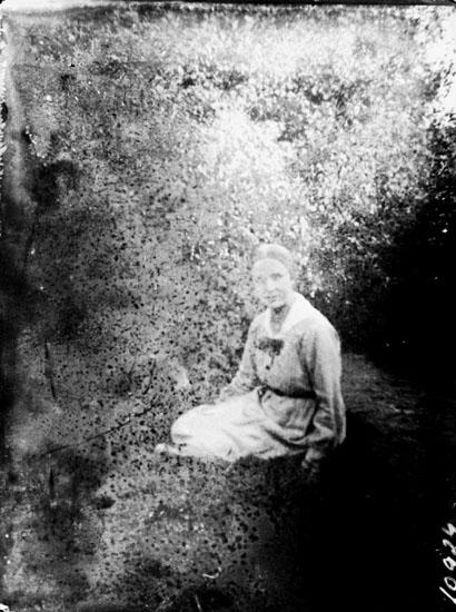 En kvinna sittande i gröngräset.