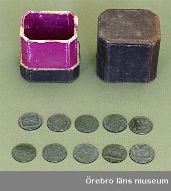 Etui med spelmarker.a) Svart rektangulär pappetui med avhuggna hörn. Fodrat med violett papper.b) Tio stycken runda marker av brons. Varje marker har på ena sidan en rektangulär platta med ett vapen och på andra sidan en rektangulär platta med en  (1 st.), två ( 3 st. ), tre ( 3 st.) eller fyra ( 3 st.) prickar.Mått: a) Längd: 60 mm. Bredd: 50 mm. Höjd: 70 mm. b) Diam: 22 mm.Gåva av fröken Maria Furtenbach, Örebro.