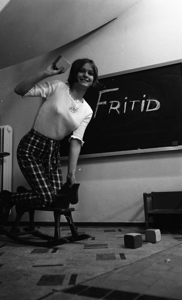 """Modebilder 23 april 1966En ung kvinna står på knä på en gunghäst iklädd vit blus, rutiga byxor och svarta lågklackade skor. Hon skrattar och håller en lekkolss i sin högra hand. Det är en modebild. Bakom henne finns en rittavla där någon skrivit ordet """"Fritid"""" med krita. Lekklossar och en liten låg barnstol står på golvet bl.a."""