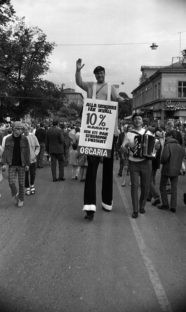 Marknadsafton 16 juni 1967.  Mannen på styltor är Leo Eide/Leonard Eidsheim och dragspelaren är Conny Sahm.