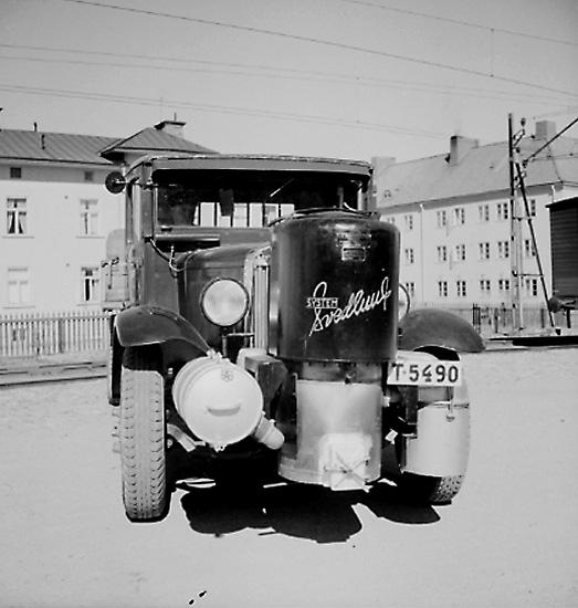 Lastbil med gasgenerator frammonterad. Bostadshus i bakgrunden, korsningen Norra Grev Rosengatan/Skolgatan, till höger huset som kallades singsing.
