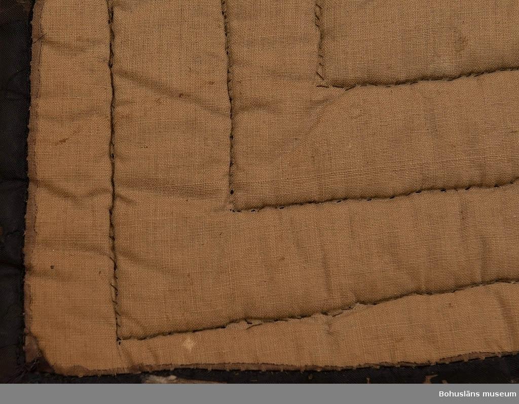 Vaddtäcke för säng så kallat dubbeltäcke, sidentäcke med bomull på undersidan. Täckets ovansida är svart med mittparti i gulgrönt med lilafärgat mönster. Mittpartiet troligtvis en infälld schal eftersom det finns en bård runt kanten. I mitten på kortändarna finns svart mönstrat parti, troligtvis en schal som delats på mitten och fällts in. Kviltat; bland annat med former av hjärtan i rader. I ett hjärta i hörn har en vinröd tråd dragits igenom. Täcket är i gott skick endast något trasigt i kanterna. Sytt omkring 1860 då Bertil Ohlssons farmorsmor gifte sig i Jörlanda. Bertil Ohlssons farmor född 1861 använde senare täcket; hon var bosatt i Sävelycke.