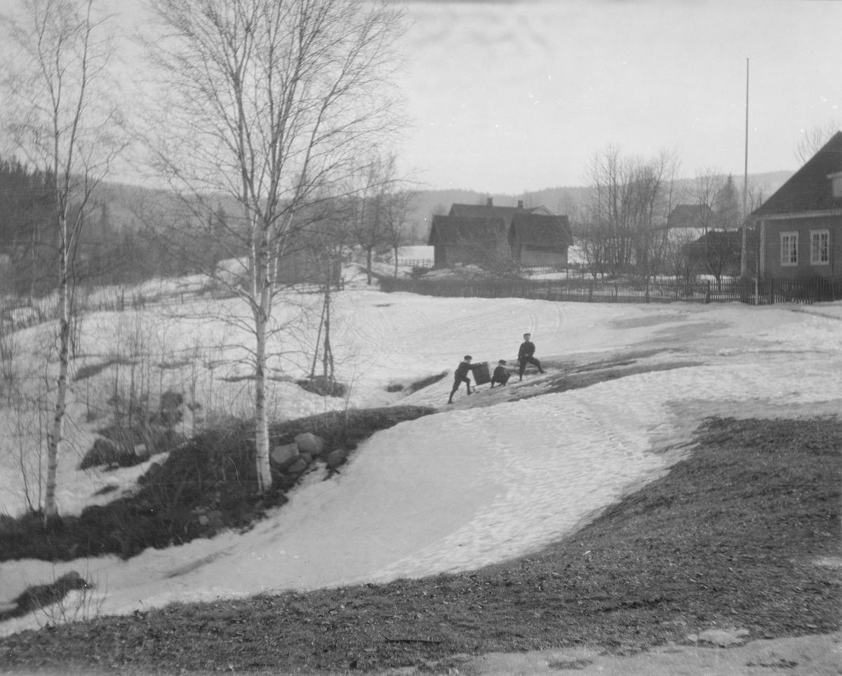 Lett bakket kulturlandskap. Litt bebyggelse, en hage og skråninger med bjørketrær i snøsmeltingstiden. Tre gutter drar noe tungt på en kjelke opp en isete bakke.