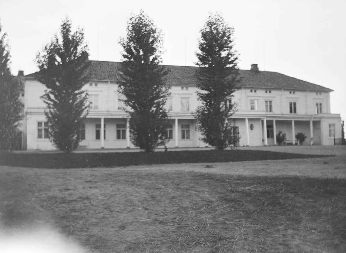 Forsiden av hovedbygningen på Linderud Gård. Foran huset står det beskårne trær i en rad.