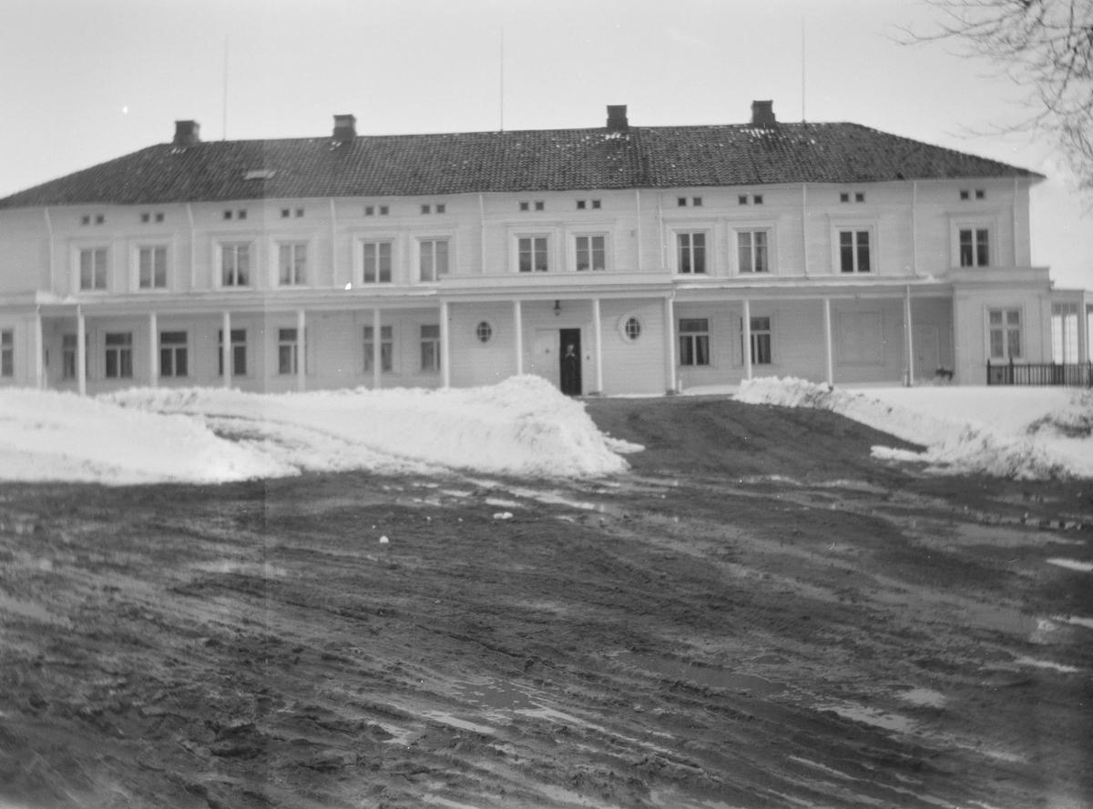 Hovedhuset på Linderud gård med gårdsplassen i forgrunnen.  Gårdsplassen er full av snøfonner og søledammer. Det skimtes en person i døråpningen.